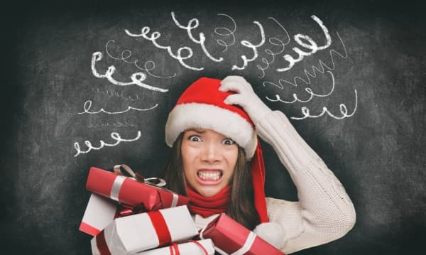 Woman in santa hat with presents, stressed out, holidays, medspa
